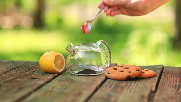 Thumbnail for Woman Brewing Black Tea in a Transparent Teapot. Breakfast on the Nature with Cookies