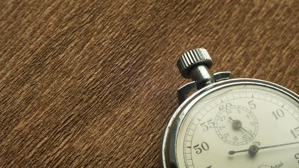Vintage White Stopwatch on the Brown Structural Background Rotates the Arrow