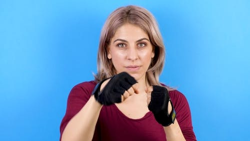 Woman Practicing Kickboxing in Sport Gloves
