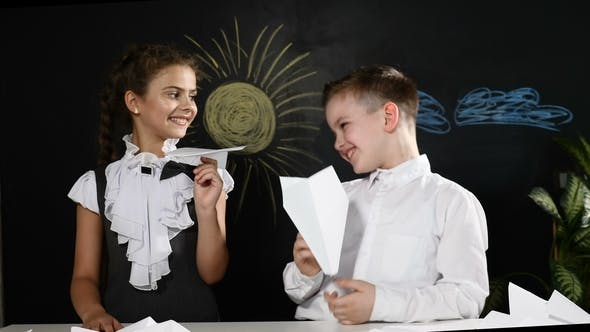 School Concept. Cute Boy and Attractive Girl Sit with Paper Planes in Hands. Desk and Blackboard