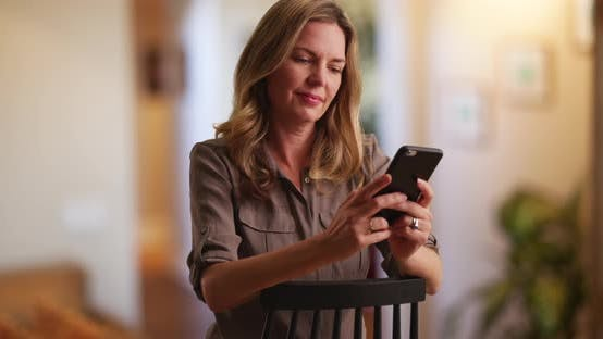 Thumbnail for Woman messaging on smartphone inside home, seated on chair