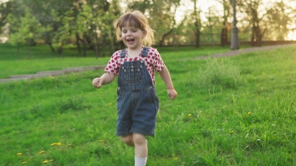 Thumbnail for Happy Little Girl Running on Green Grass at Sunset in Sunny Summer Day