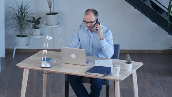 Thumbnail for Businessman Work on Computer While Talking on Smart Phone