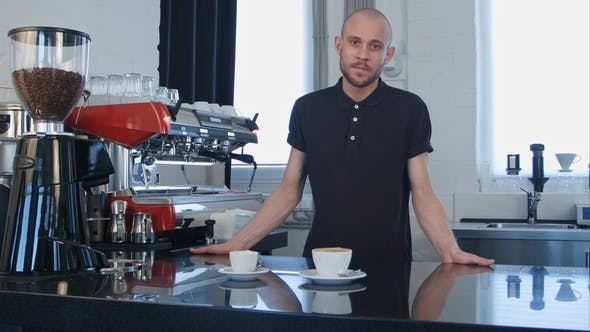 Thumbnail for Portrait of a Young Smiling Male Barista Holding Cup of Coffee at the Cafe