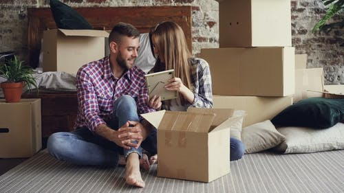 Married Couple Is Unpacking Personal Things While Sitting on Floor in New House. Young People