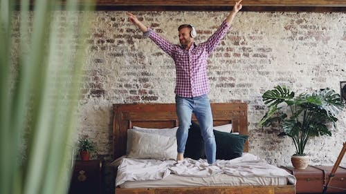 Young Bearded Man Dancing on Double Bed and Listening To Music in Headphones. Modern Loft Style