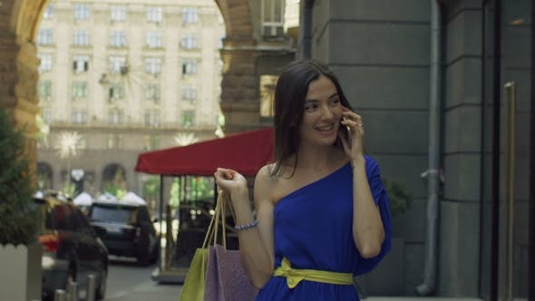 Thumbnail for Cheerful Woman with Shopping Bags Talking on Phone