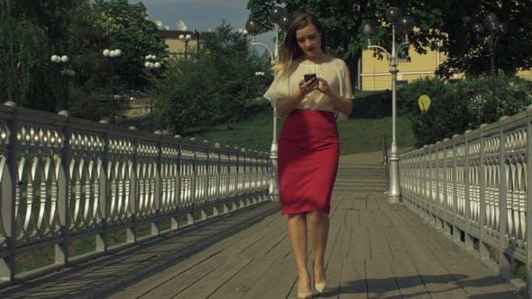 Thumbnail for Stylish Woman Using Smart Phone App on City Bridge