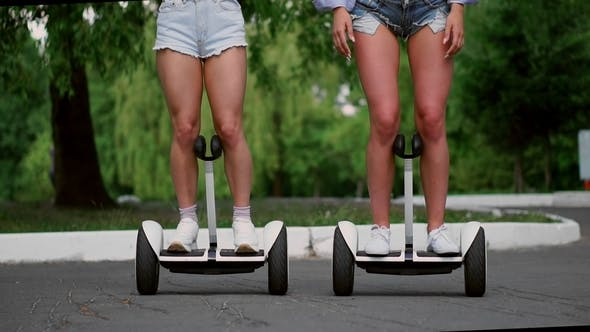 Thumbnail for Two Sexy Young Girls Riding on Segway in Short Shorts Holding Hands and Laughing on a Sunny Day in