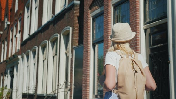 Cover Image for A Young Woman with a Pink Backpack Enjoys a Stroll Through the Ancient Street of the European City