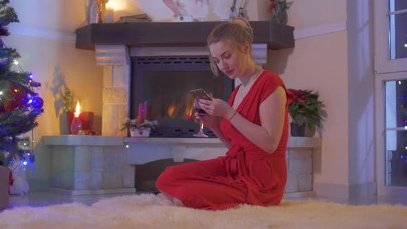Thumbnail for Young Girl in Red Dress Sit on Floor Near Christmas Tree and Using Her Phone