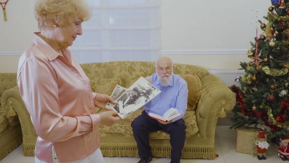 Thumbnail for Senior Woman Look Her Old Photos, Her Husband Read Book Sitting at Sofa