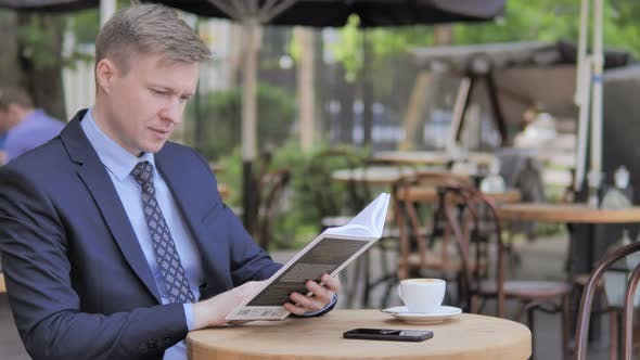 Thumbnail for Outdoor-Sitzender Geschäftsmann Lesebuch