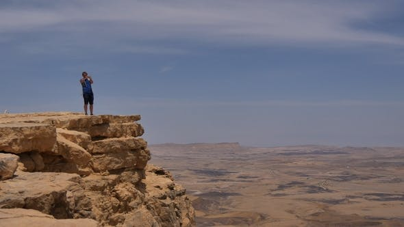 Thumbnail for Young Man Standing on Cliff Edge and Taking Pictures of the Desert on His Phone