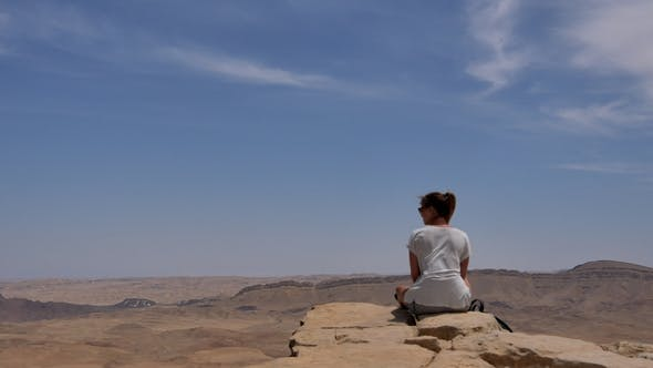 Thumbnail for Young Woman Sitting on Cliff's Edge and Looking at the Desert