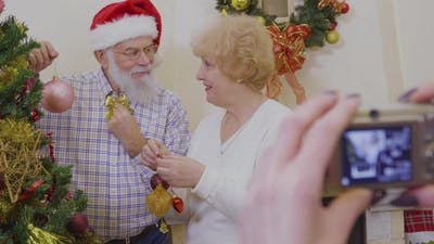 Happy Old Couple Decorate Christmas Tree Together