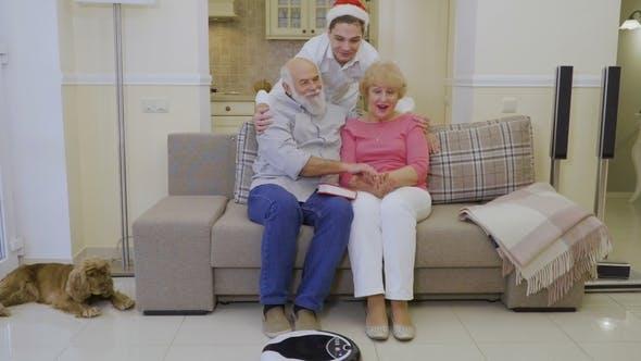 Grandson in Santa's Hat Hugs Grandparents