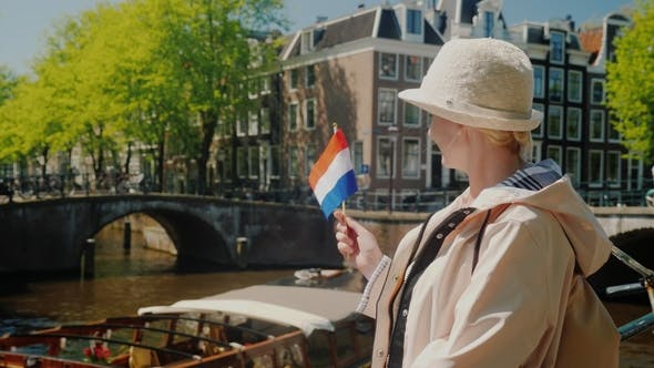 Thumbnail for A Woman with the Flag of the Netherlands in Her Hand Admires the Beautiful View of the Canal in