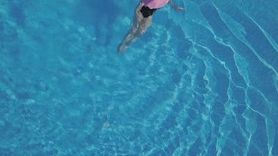 Young Woman Swimming in a Swimming Pool