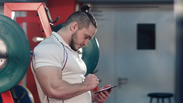 Thumbnail for Bodybuilder Using Digital Tablet to Track His Workout Progress in Gym