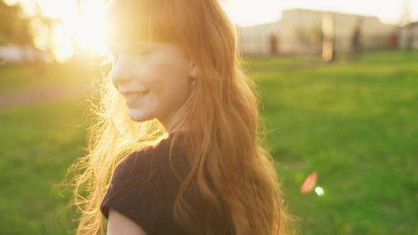 Thumbnail for Happy Ginger Girl Walking and Looking Into Camera at Sunset in Summer Park