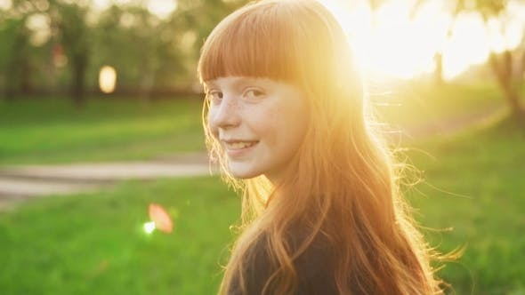 Thumbnail for Happy Girl with Red Hair Walking, Looking Into Camera and Smiling at Sunset