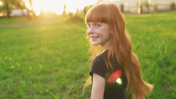 Cover Image for Little Beautiful Redhead Girl Goes To Meet Sun and Looks Into Camera