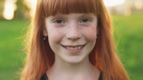 Face of Happy Ginger Girl with Freckles on Blurred Background