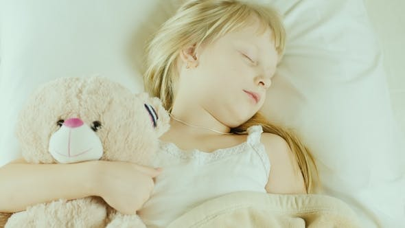 Thumbnail for Little Girl Is Sleeping in Bed. Cuddles a Toy Bear