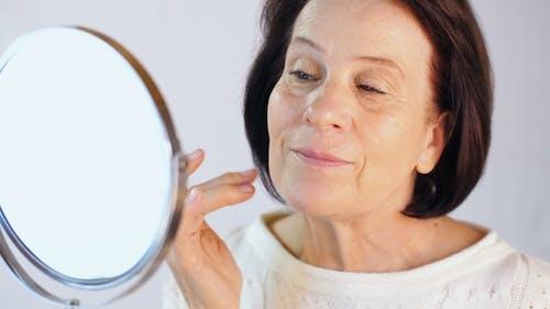 Frau befeuchtet das Gesicht mit Creme