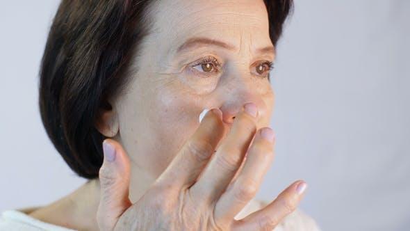 Thumbnail for Frau mittleren Alters Anwendung Creme auf Gesicht