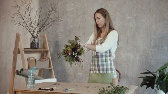 Thumbnail for Charming Florist Arranging Flowers in Florist Shop