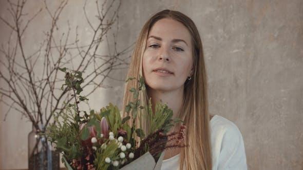 Thumbnail for Florist Holding Freshly Assembled Flower Bouquet