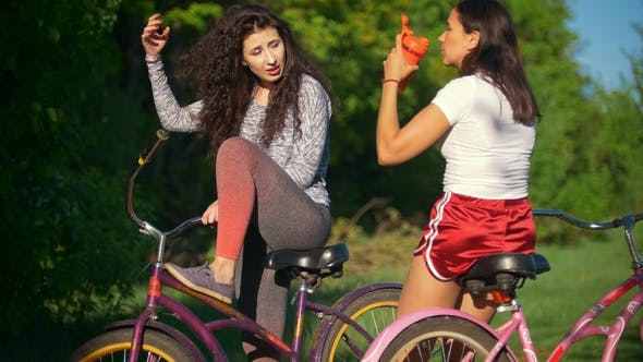Thumbnail for Rest on a Bike Ride, Two Female Cyclists Drink Water and Talk , Sunny Summer Day
