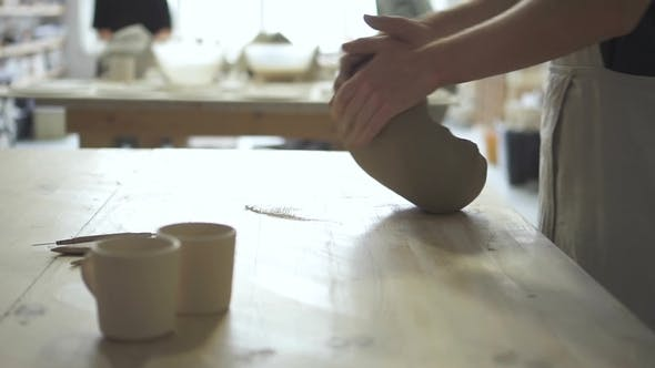 Thumbnail for Young Potter Is Kneading Clay Mass on Table in Pottery Workshop.