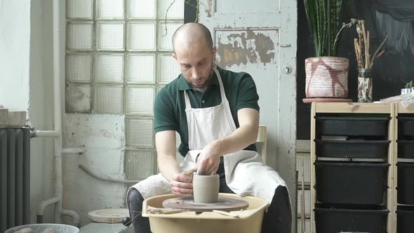 Thumbnail for Portrait of Male Professional, Who Is Making Loam Pot in Bright Studio.