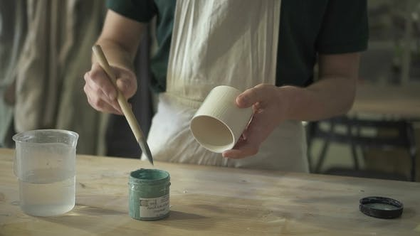 Thumbnail for At the Desk Artist Paints a Clay Mug with a Blue Brush