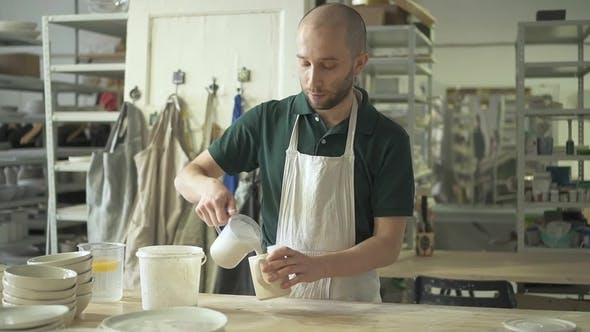 Thumbnail for In Workshop Craftsman Pours Liquid From Tank Into a Mug of Clay