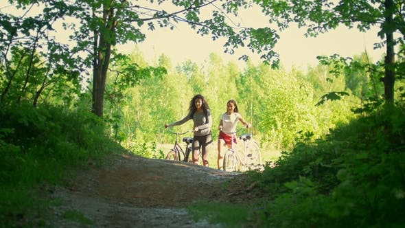 Thumbnail for A Bike Ride in the Forest, Two Girlfriends of the Cyclist Have Fun Communicating and Climb From the