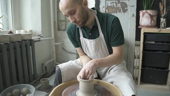 Thumbnail for In Pottery Workshop Man Quickly Makes High Mug with Hands on Potter's Wheel.
