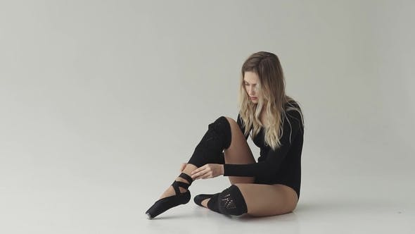 Thumbnail for Ballet Dancer Ties Her Pointe Shoes Sitting on the Floor. Young Girl Dancer in Black Bodysuit