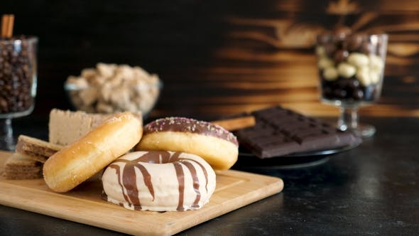 Thumbnail for Three Donuts on Wooden Board Next To Different Type of Candy