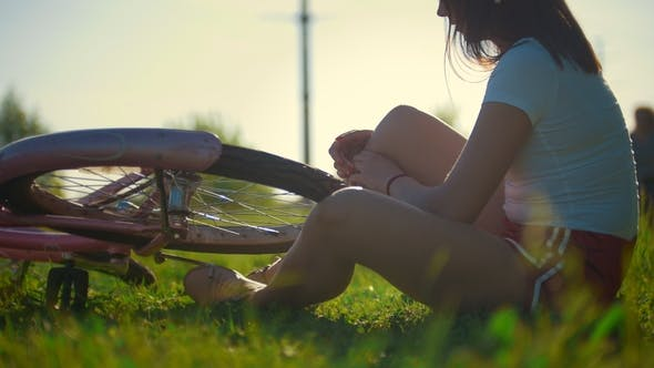 Thumbnail for Girl Sitting on the Grass and Scrolls the Wheel of a Bicycle, in the Background Riding Another Girl
