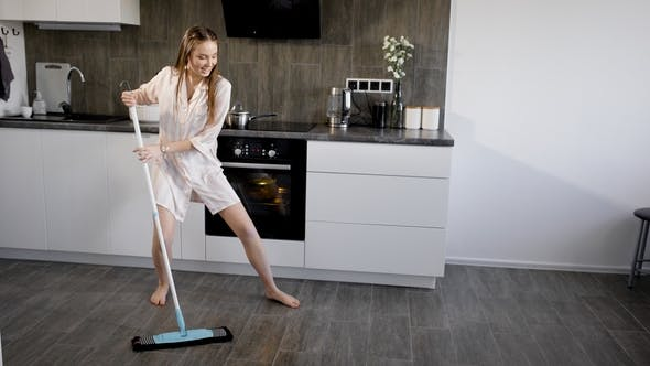 Pretty Young Woman Cleaning Up in Kitchen