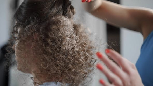 Stylist Makes Curly Afro Hairstyle for Woman By Hot Curling Hair, Process of Making Hairstyle
