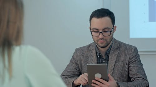 Male Teacher in Class Room Giving the Subject Using Tablet