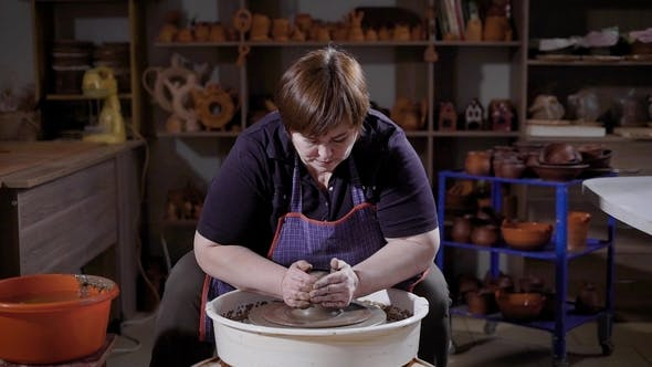 Thumbnail for Female Master Wearing Apron Sitting and Shaping Clayware on Potter's Wheel in Workshop