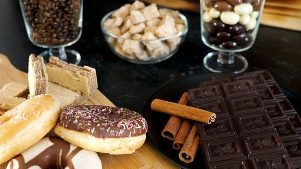 Thumbnail for Donuts and Waffles Next To Dark Chocolate and Cinnamon Sticks