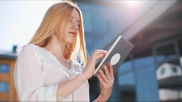 Thumbnail for Pretty Young Blonde Woman Using Tablet Computer Device Outside on the Street. Woman Smiling, Tapping
