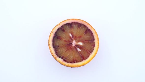 Thumbnail for Half of Blood Orange. Slice of Red Orange Rotating on the Turn Table. Isolated on White Background